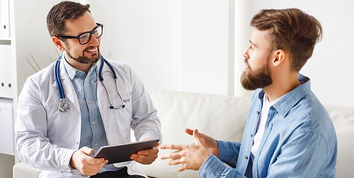 Врач с пациентом беседуют сидя на диване